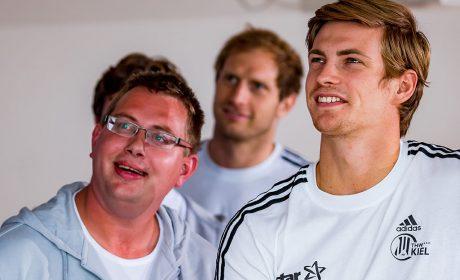 """Pierre Petersen, Steffen Weinhold und Rune Dahmke schauen sich bei der Pressekonferenz das Making-of zum Fotoshooting der """"Gesichter der Spiele"""" an. (Foto: SOD/Sascha Klahn)"""