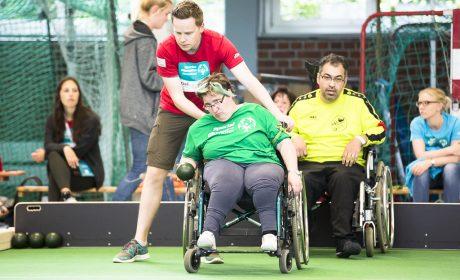 Ein Helfer richtet den Rollstuhl von Kerstin Will (Antonius-Netzwerk Fulda) nach ihren Wünschen aus, damit sie die Bocciakugel möglichst nah an den Pallino rollen kann. (Foto: SOD/Stefan Holtzem)