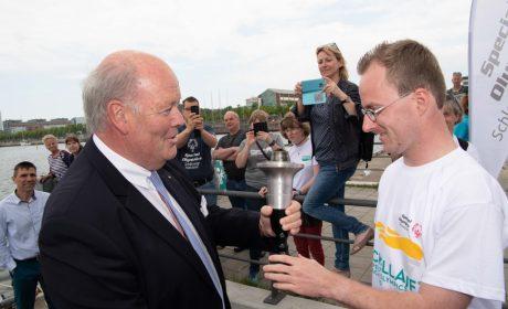 Die Fackel wird von Innenminister Hans Joachim Grote an Sebastian Kröger, Athletensprecher der Special Olympics Schleswig-Holstein, übergeben. (Foto: SOD/Michael Richter)