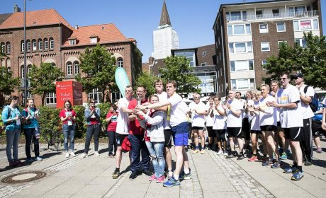 Die Läuferinnen und Läufer haben mit OB Ulf Kämpfer das Ziel an der Sparkassen-Arena-Kiel erreicht und präsentieren die Special Olympics Fackel. (Foto: SOD/Stefan Holtzem)