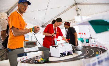 Besucherinnen und Besucher im Zelt der ABB probieren sich an der Carrera-Bahn aus. (Foto: SOD/Sarah Rauch)